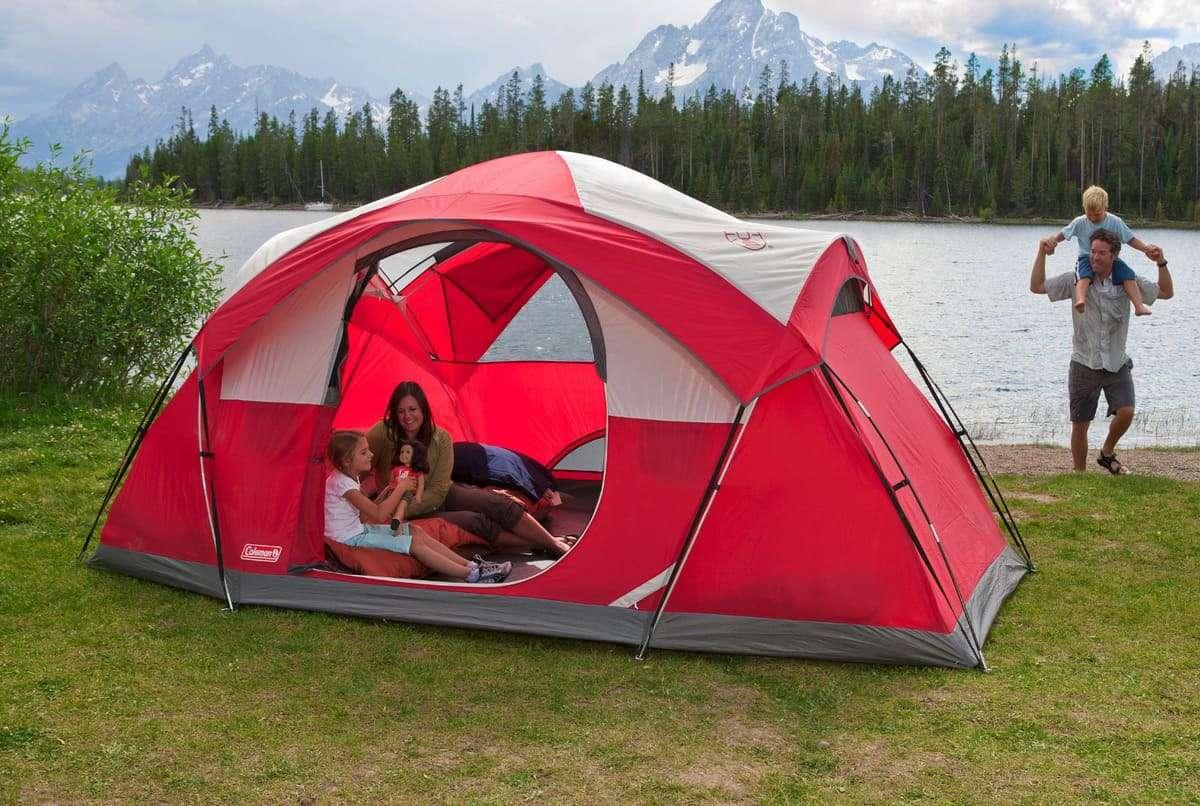 Familia en tienda de campaña al lado de un lago de montaña