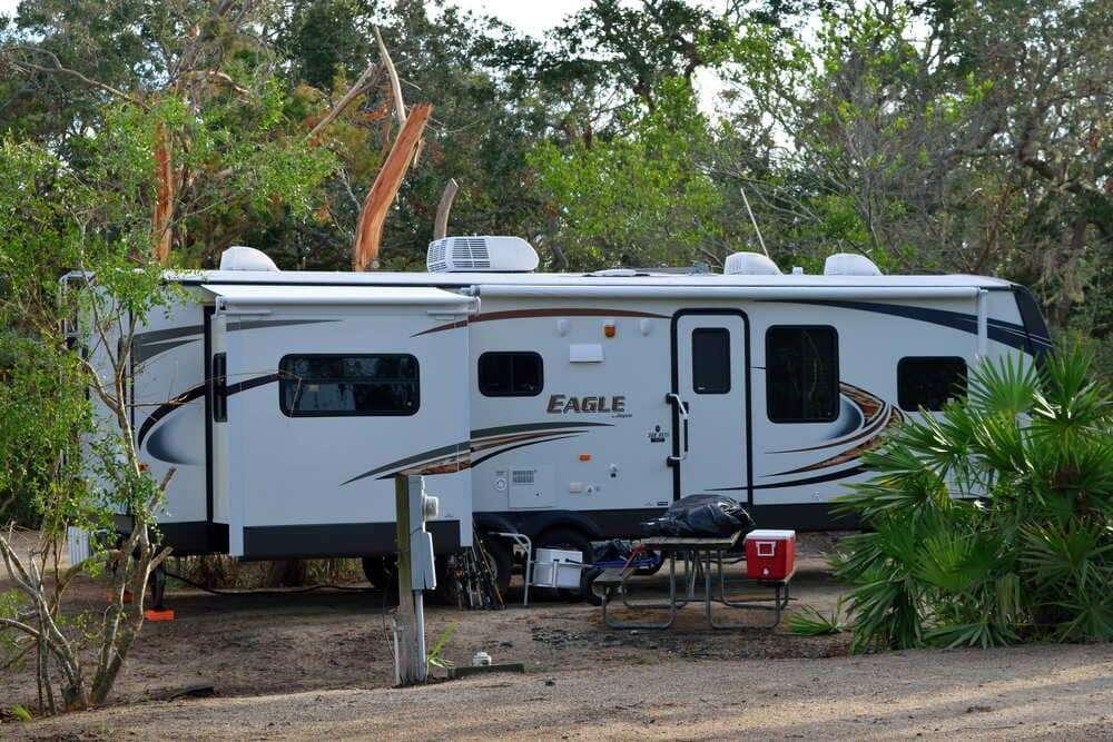 Caravana de grandes dimensiones estacionada en camping en plena naturaleza